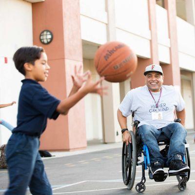 alumnus watching boy catch basketball