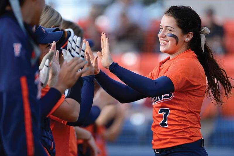 Softball player celebrating with team